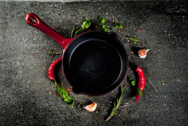 Cooking background with skillet and spices - hot pepper, garlic, basil, rosemary, salt, black stone table Premium Photo