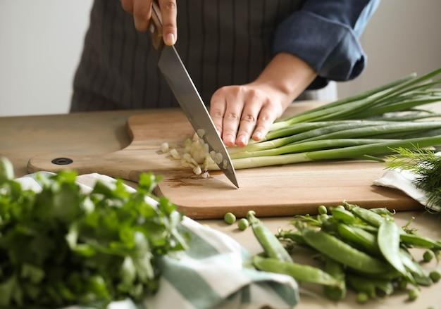 Готовка. шеф-повар режет зелень на кухне Бесплатные Фотографии