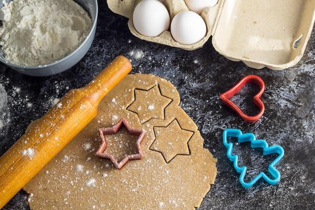 Cooking christmas gingerbread cookies  ingredients ondark background Premium Photo