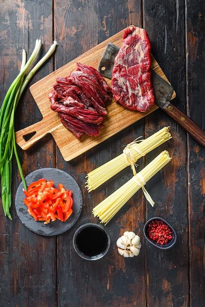 소고기와 함께 볶은 야키소바를 만들기위한 요리 재료. 플랩 스테이크와 국수 나무 배경입니다. 프리미엄 사진