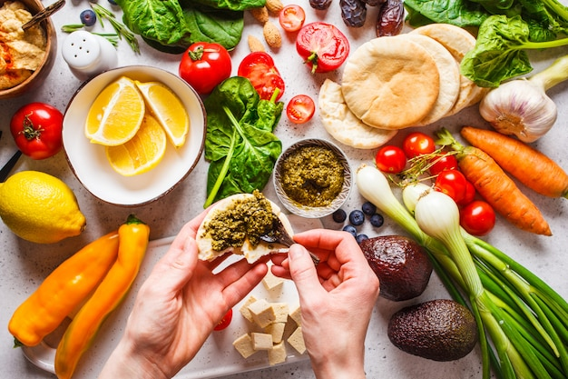 Cooking healthy vegetarian food background. vegetables, pesto and fruits on white background. Premium Photo