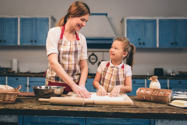 Cooking homemade cakes. happy loving family are preparing bakery together. mother and child daughter girl are cooking cookies and having fun in the kitchen. roll the dough. Premium Photo