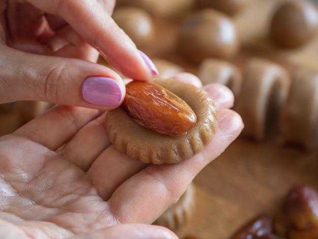 自家製イードデートのお菓子を調理します。アラビア語ラマダンのお菓子 Premium写真