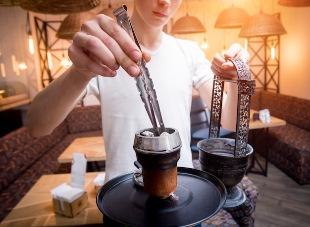 Cooking hookah in the bar. young man with hookah in restaurant, hookah bar, smoking cafe. Premium Photo