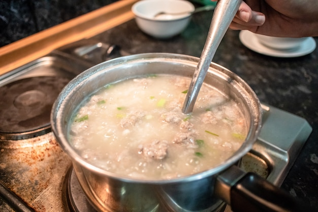 Cooking hot ground pork congee. Premium Photo