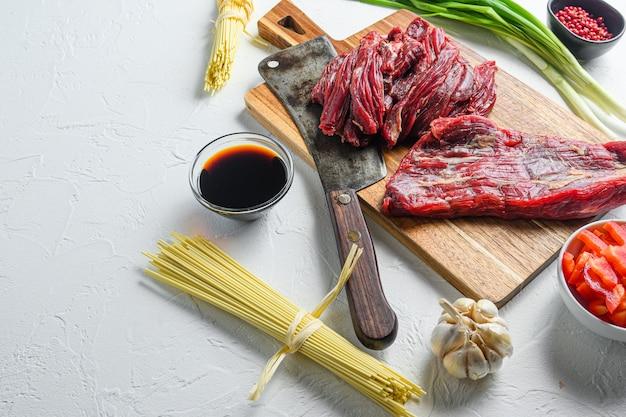 소고기를 넣은 야키소바 볶음 요리 재료. 텍스트에 대 한 공간을 가진 흰색 테이블에 측면보기. 프리미엄 사진