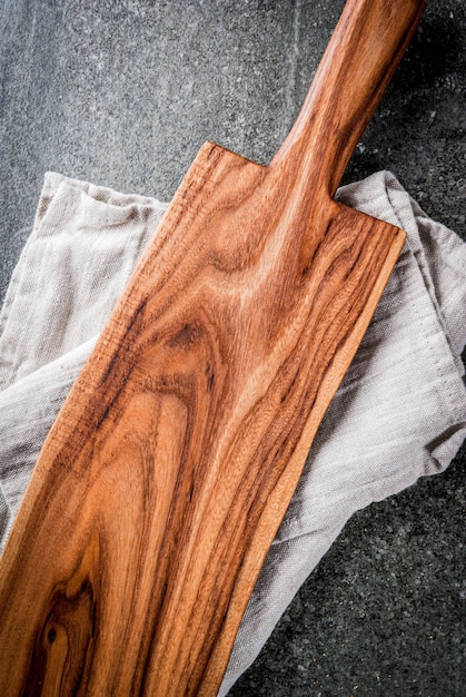 Cooking , old wooden cutting board with kitchen towel on black stone table. top view, copyspace Premium Photo