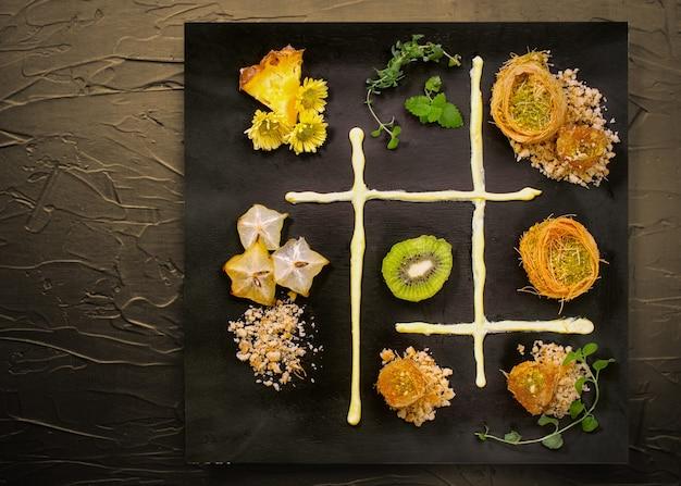 요리 과자 터키 전통 라마단 과자 디저트 Kunafa (kadaif, 바클 라바), 키위, 파인애플, 견과류, 어두운 배경. 플레이트 아트 구성. 프리미엄 사진
