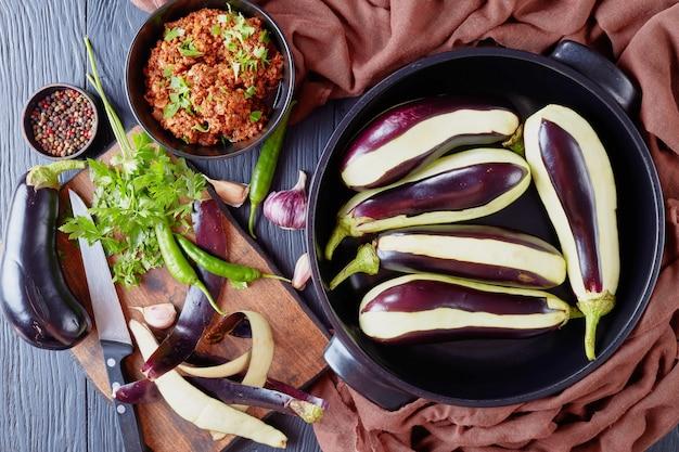 Готовим фаршированные баклажаны, баклажаны с мясным фаршем, помидорами и луком. ингредиенты на деревянном столе, вид сверху, плоская планировка Premium Фотографии