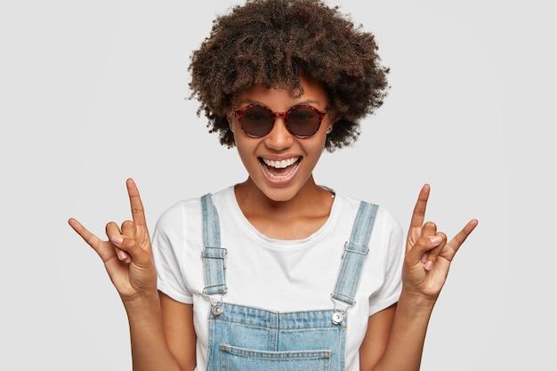 音楽スターであるクールなアフリカの女性は手を上げてロックのシンボルを作ります 無料写真