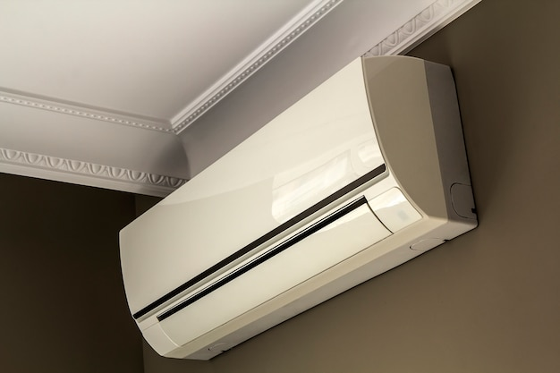 Cool air conditioner system on dark wall in room interior Premium Photo