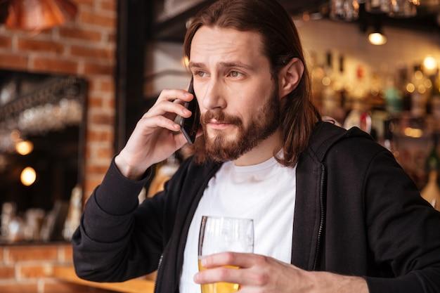 バーの近くの電話で話しているクールなひげを生やした男 無料写真