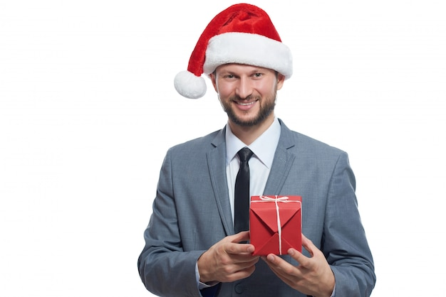 Cool businessman. portrait of handsome man wearing christmas hat posing with small gift in hands. Premium Photo