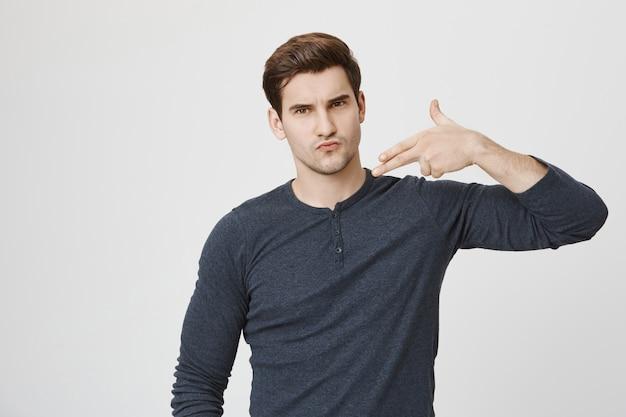 Крутой уверенный в себе парень, показывающий жест пистолета Бесплатные Фотографии
