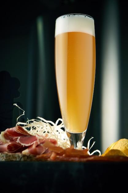 Холодное крафтовое пшеничное пиво в длинном бокале с закусками Premium Фотографии