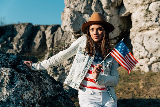 Cool female holding us flag standing on rocks Free Photo