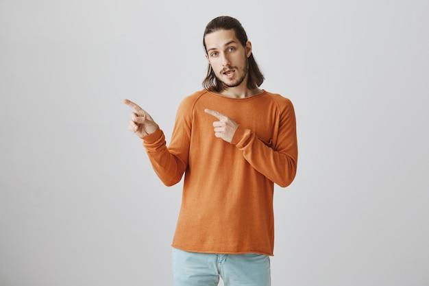Fresco bel ragazzo hipster che punta il dito a sinistra, invitando a dare un'occhiata Foto Gratuite