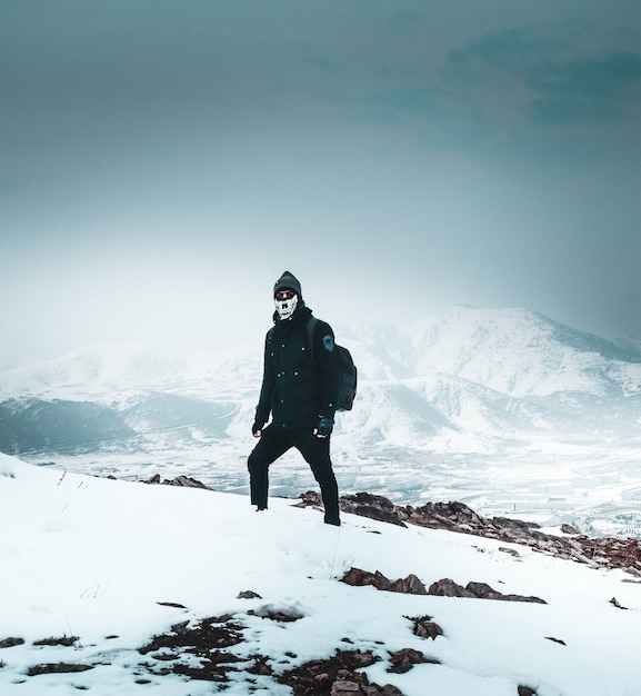 山の中の雪の急な丘の上に一人で立っているマスクと暗い服を着たクールなハイカー 無料写真