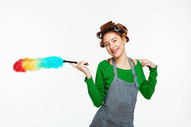 Cool housewife smiles  holding duster in hands Free Photo