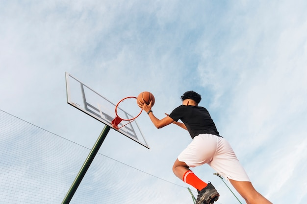 Cool sporty man throwing basketball into hoop Free Photo