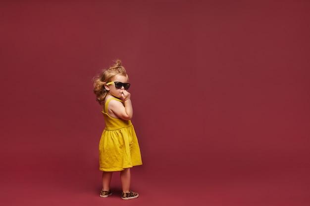 노란 드레스와 선글라스와 선글라스 분홍색 배경에서 격리에 멋진 세련 된 소녀. 아동 패션. 공간 복사 프리미엄 사진