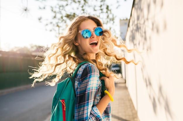 Donna bionda felice sorridente elegante fresca che cammina in strada con lo zaino Foto Gratuite