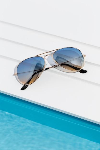 小さなプールの横にあるクールなサングラス 無料写真
