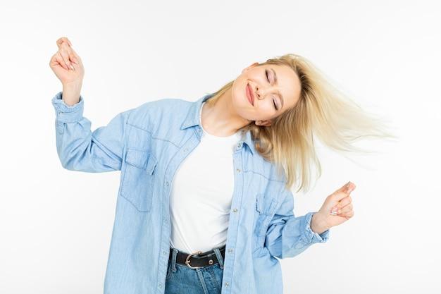 Крутая молодая энергичная девушка танцует на белом фоне студии Premium Фотографии