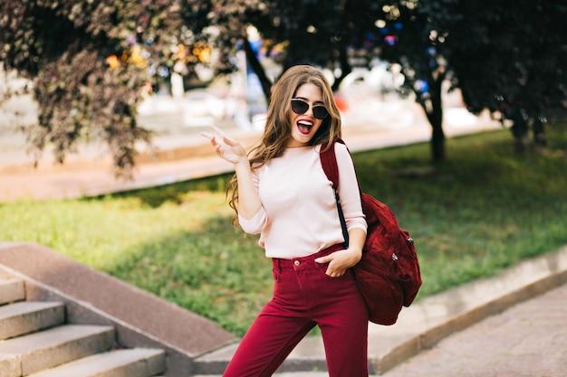 Ragazza fresca con borsa vinosa e capelli ricci lunghi divertendosi nel parco in città. indossa il colore del marsala e sembra eccitata. Foto Gratuite