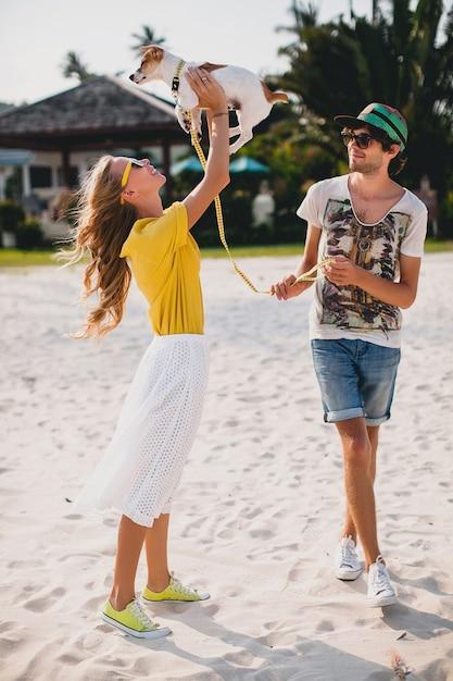 クールな若いスタイリッシュな流行に敏感なカップルの愛の散歩とビーチで犬と遊ぶ 無料写真