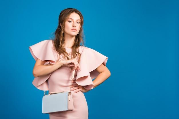 핑크 럭셔리 드레스, 여름 패션 트렌드, 세련된 스타일, 블루 스튜디오 배경, 유행 핸드백을 들고 멋진 젊은 세련된 섹시한 여자 무료 사진