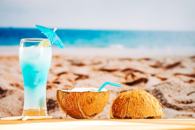 Cooling blue cocktail and coconut milk on sandy beach Free Photo