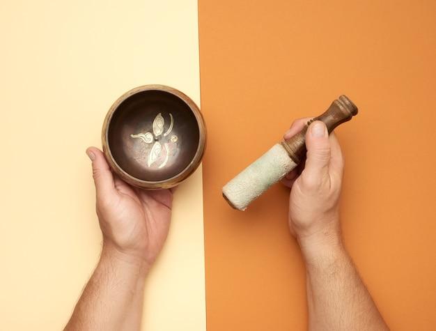 Медная поющая чаша и деревянная палочка в мужской руке, вид сверху Premium Фотографии