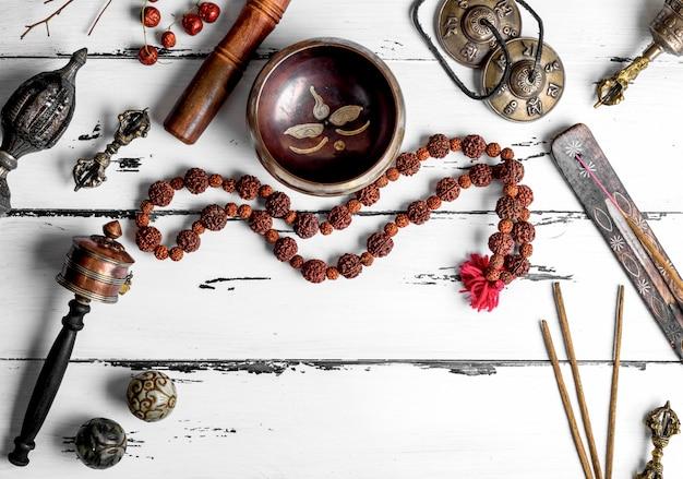 Copper singing bowl, prayer beads, prayer drum, stone balls and other tibetan religious objects Premium Photo