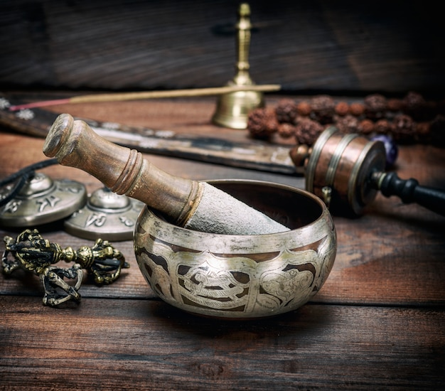 Copper singing bowl and a wooden stick on brown table Premium Photo