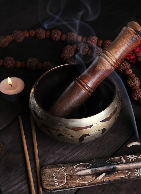 Copper singing bowl and a wooden stick on a brown table Premium Photo