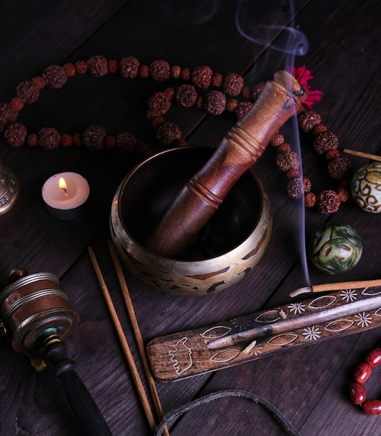 Copper singing bowl and a wooden stick Premium Photo