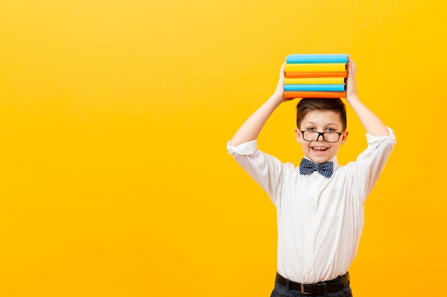 Copy-space boy holding stack of books Free Photo