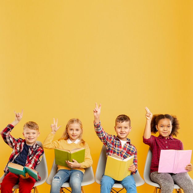 Copy-space childrens with arms raised to answer Free Photo