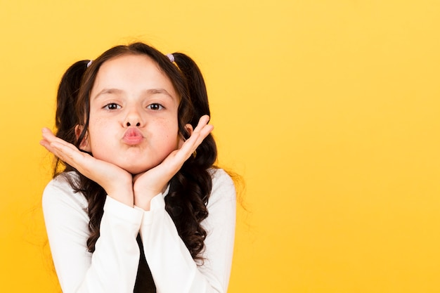 Copy-space cute little girl kiss pose Free Photo