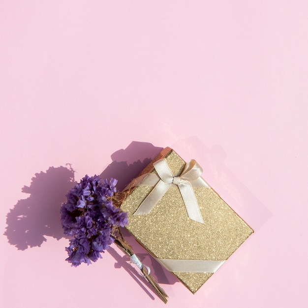 Copy space cute wrapped gift with flowers Free Photo