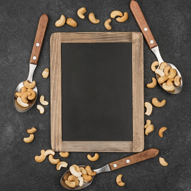 Copy space frame and spoons filled with cashew nuts Free Photo