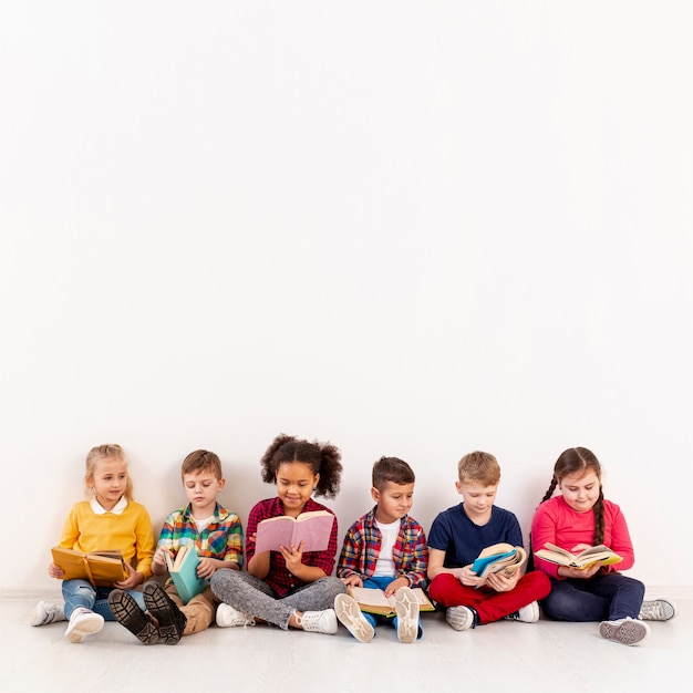 Copy-space group of childrens on floor reading Free Photo