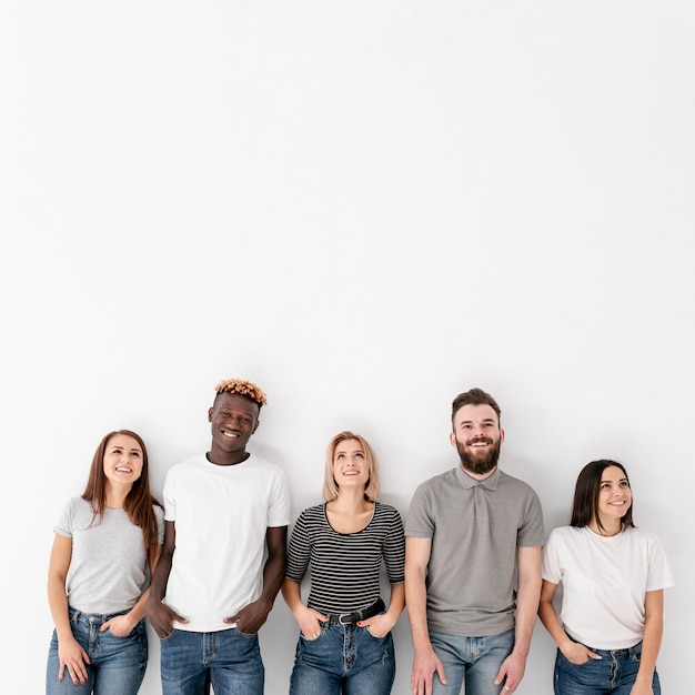 Copy-space group of friends standing next to wall Free Photo