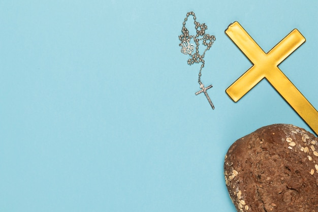 Copy-space holy cross and necklace with bread Free Photo