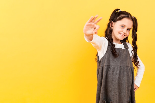 Copy-space little girl showing ok sign Free Photo