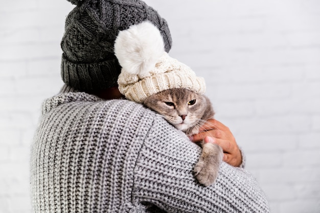 Copy-space male and cat wearing fur cap Free Photo