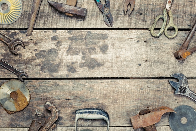 Copy space on old wooden background with vintage rusty tools Premium Photo