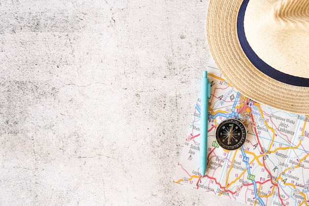Copy space straw hat and map elements Free Photo
