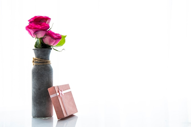 Copy space vase of roses with gift Free Photo